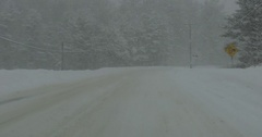 Driving plate POV in blowing snow whiteout and blizzard in squalls Stock Footage