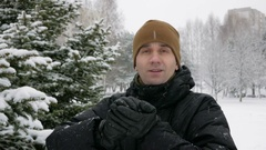 A young man looking at the camera and playing with snow in winter forest. It Stock Footage