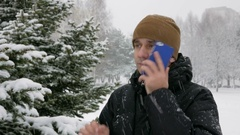 A young man in winter forest talking on the phone. Big snowfall. He admires the Stock Footage
