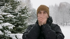 A young man in winter is cold in the forest near the spruce. Big snowfall. He's Stock Footage
