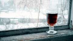 Snow falling on glass cup with tea on window sill Stock Footage