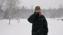 A young man drinking a hot beverage from a thermos in a winter forest. Big Stock Footage