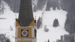 Chapel with a clock in front of the ski slope Stock Footage