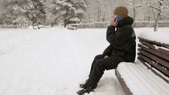 A young man in winter park talking on the phone. He admires the sides of snow Stock Footage