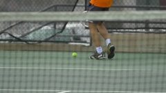 Male tennis player gathering tennis balls with racket , slow motion. Stock Footage