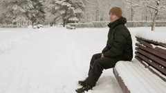 A young man sits on a bench in winter park and admiring the snow. A man in a Stock Footage
