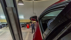 Car mechanic drive red car from lift to wheels alignment camber check at repair Stock Footage