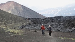 Female tourists walking on trail on background of lava flow and cone of volcano Stock Footage