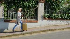 Woman with travel bag goes along the resort area Stock Footage