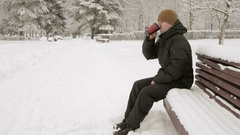 A young man drinking a hot beverage from a thermos in a winter park. Big Stock Footage