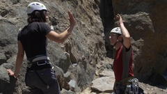 """A couple celebrating and slapping hands giving a """"high five"""" while rock climbing Arkistovideo"""