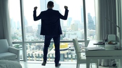 Successful businessman raising arms by window, power symbol, super slow motion Stock Footage