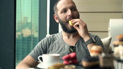 Young man eating tasty dessert and drinking coffee sitting in cafe Stock Footage
