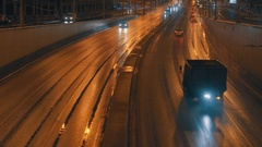 Cars going on night city street in golden light Stock Footage