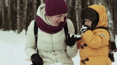 Young mother plays with her son in snowy park Stock Footage