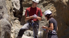 "A couple celebrating and slapping hands giving a ""high five"" while rock climbing Stock Footage"