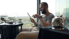 Young man surfing web on tablet and eating tasty dessert in cafe Stock Footage
