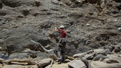 A young man pulling his rope down after rock climbing. Stock Footage