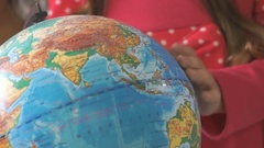 Little girl rotates the globe of world. Close-up Stock Footage
