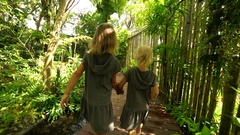 Two little sisters walking in a beautiful tropical garden. Steadicam shot Stock Footage