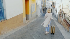 Woman tourist with travel bag on wheels goes down the narrow street of the old Stock Footage