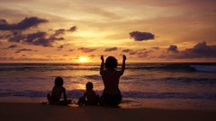 Happy mother with two baby daughters having fun on the ocean at sunset Stock Footage