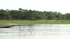 A motorized canoe along the lake shore a Malian. Silhouette of the fisherman. Stock Footage