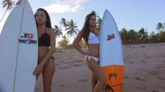 Surrounding Two Beautiful Attractive Surf Girls Standing Up Holding Surfboard Stock Footage