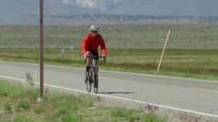 A man road biking on a scenic road. Stock Footage