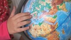 Child twists model of globe of world. Close-up Stock Footage