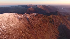 Slow drifiting aerial view of Crib Goch and Snowdonia at sunrise. Stock Footage