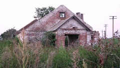 The old, ruined farm, without a roof in the thickets on the field Stock Footage