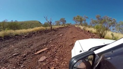 4x4 Vehicle driving over red rocks to top of Mount Nameless Stock Footage