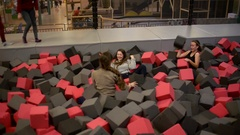 Girls play in the pit with foam smiling having fun Stock Footage
