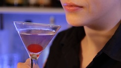 Woman drinks alcoholic cocktail with cherry, close up. Beautiful lips. Aviation Stock Footage