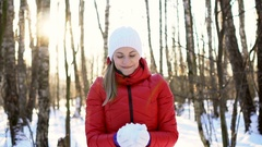 Attractive young woman in sunny winter park, playing with the snow, having fun Stock Footage