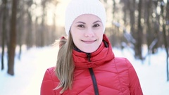 Beautiful young woman running in winter park, inviting to join, smiling, and Stock Footage