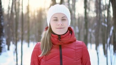 Beautiful young woman standing in winter park, smiling, taking a deep breath Stock Footage
