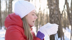 Beautiful young woman blowing snow in winter park, having silly fun, smiling Stock Footage