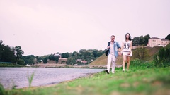 Guy and girl walking along the river Stock Footage
