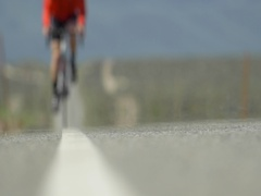 A man road biking on a scenic desert road, slow motion. Stock Footage