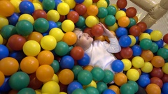 Kid girl playing in the pit of colored balls Stock Footage