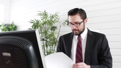 Accounting Manager looks over file in corporate office setting Stock Footage