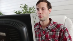 Man stares in trance at computer screen Stock Footage