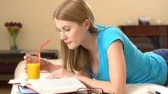 Beautiful college student in glasses lying on sofa and studying. Drinking orange Stock Footage