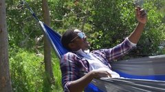 A man taking a selfie with his mobile device while resting in a hammock near a m Stock Footage