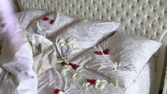 Nice bed with white bedclothes decorated with rose petals Stock Footage