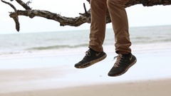 Dangling legs from male sitting on branch at beach Stock Footage