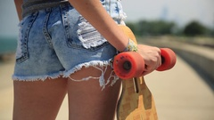 Detail of a young woman and her longboard skateboard. Stock Footage