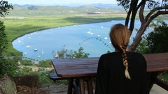 Female sitting on table above Cooktown bay Stock Footage